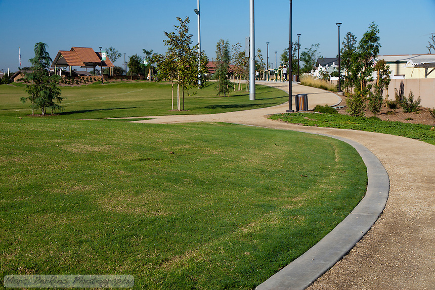 The walking path, along with some exercise equipment, grass lawn, and bandstand of Stanton Central Park.