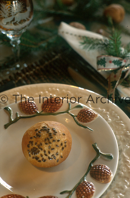 Close up of a freshly baked seeded roll served on a ceramic plate with a fruit motif decoration