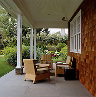 The porch on one side of the shingle-clad property overlooks the garden