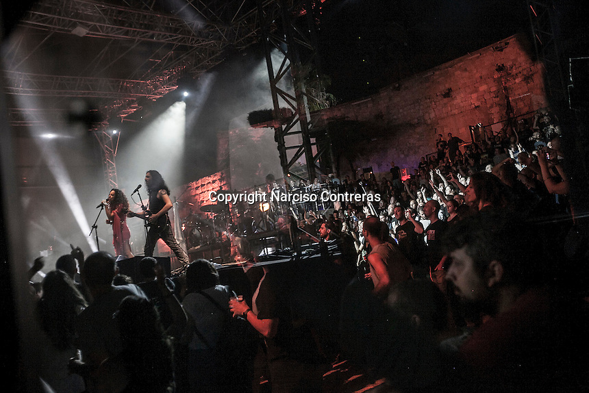 August 27, 2014 - Binyamina, Haifa District, Israel: Shlomit Levi (left) and Idan (right), singer and guitar player at Orphaned Land heavy metal band, are seen reflected in a safety glass as they perform a concert in Binyamina Amphitheatre at north of Israel. Orphaned Land is a music band founded by Jewish and Arabian musicians who combine ethnic music with rock metal as they recite verses in Hebrew and Arabic from the sacred Quram and Tora Scriptures. (Narciso Contreras/Polaris)