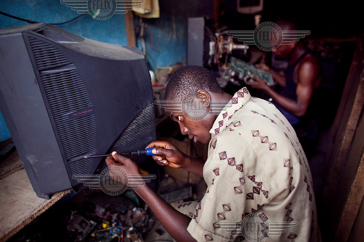 Technicians try to repair televisions at the Alaba Electronics Market. British firms have come under fire for charging people to collect their electronics, including televisions and computer monitors for recycling, and then shipping them to Nigeria to be sold.