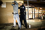 Former Sacramento Police Department robbery detective Darryl Bryan searches a suspect as a patrol officer on the graveyard shift on  October 26, 2012 in Sacramento, Calif. Budget cuts have decimated the Sacramento Police Department resulting in the elimination of many investigative units.