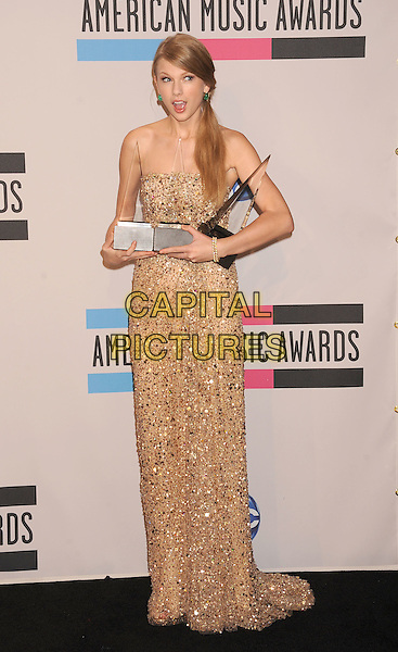 Taylor Swift.at the 2011 American Music Awards - Press Room held at Nokia Theatre at L.A. Live in Los Angeles, California, November 20th, 2011.  .AMA AMAs full length strapless gold sequined sequin beaded long maxi dress awards trophies .CAP/ROT/TM.©TM/Roth Stock/Capital Pictures