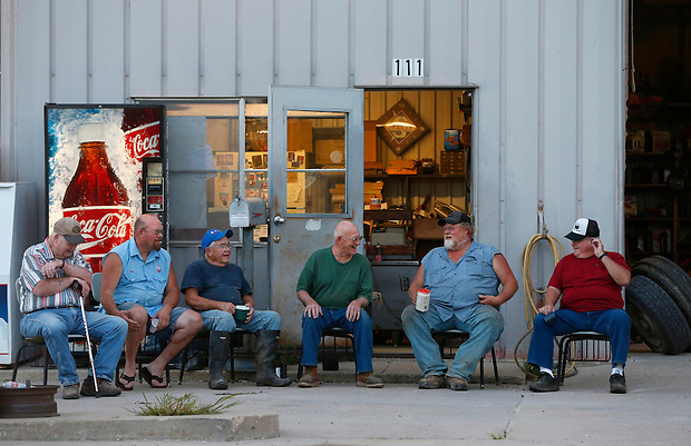 A group of Union County men gather each morning at sunrise outside Frank's Service in Arispe.  From left are Marvin Ringberg, Mike Fry, Don Wilson, Frank Eighme, Randy Needham and Jim Bradley.  They sit on relics of the past, chairs from the long gone Arispe schoolhouse, which closed in 1994. The remote, weathered station is one of the few remaining commercial businesses in the southern Iowa town of about 100.