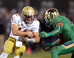 (Boston, MA, 11/21/15) Boston College quarterback John Fadule, left, is sacked by Notre Dame's Max Redfield during the second quarter as Notre Dame hosts Boston College at Fenway Park in Boston on Saturday, November 21, 2015. Photo by Christopher Evans