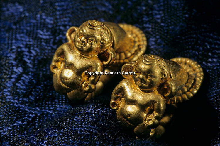Cupid ear clipd,Gold artifacts from Tillya Tepe find,  six tombs of Bactrian nomads; Discovered in 1978 by Soviet archaeologist; Thought lost but discovered in 2003 in Afghan National Bank Vault, at the Presidential Palace; saved from the  Mujahadein and Taliban; Elements of  Greek, Indian, Asian culture.