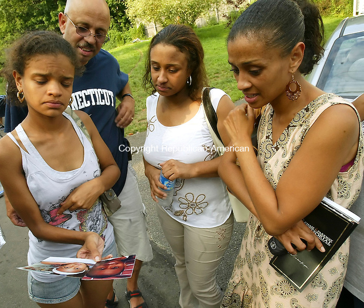 WATERBURY, CT, 15 July 2006- 071506BZ04-  Ramona Rivera, third from left, whose 8-year-old son, Royel Taft, was killed by an out of control driver who crashed through a fence and sped across her yard Friday night, looks at pictures of her son with Carmen Rivera, Royel's aunt, left, Raymond Rivera, Royel's grandfather, and Stacey Rivera, Royel's aunt, right, in the yard of her Waterville Avenue home Saturday afternoon.<br /> Jamison C. Bazinet Republican-American
