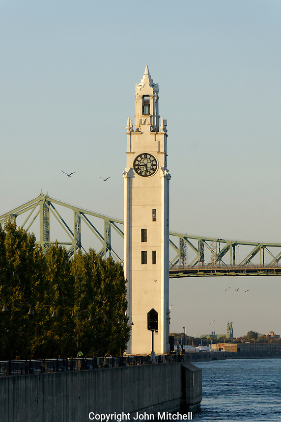 The Clock Tower located ion Quai de Horloge with with the Jacques Cartier Bridge in back, Old Port of Montreal, Quebec, Canada
