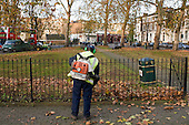 Grounds maintenance staff clear leaves from a Brent Council open space in Kilburn, London
