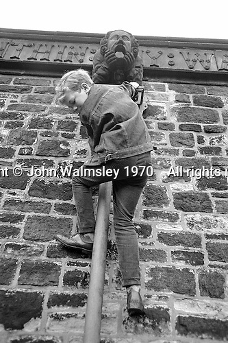 Climbing down the pipe during a trip into the locality near Whitworth Comprehensive School, Whitworth, Lancashire.  1970.