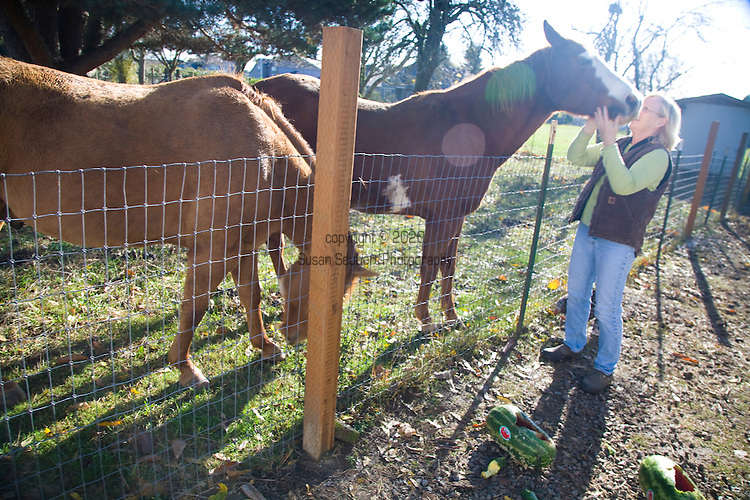 Sheryl and Dan Hall's historic Oregon City home, the White Kellogg House, an 1845 classic revival home set on 8 acres of farmland. Pictured is Sheryl Hall with two of the farm's horses.
