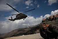 A soldier covers himself from dust as US Army General Schloesser's helicopter departs following a briefing at the Korengal Outpost in the restive Korengal Valley in Kunar. He came to Blessing for an urgent briefing on recent activity.
