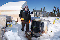 """Thursday  March 11 , 2010  Volunteer Jim Paulis stands proudly next to his invention that has been called """" The biggest dog cooker on earth """" at Cripple .  Typically mushers must melt snow at the Cripple checkpoint but Jim has made it his mission this year to provide water to each musher."""
