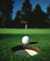 Close up of a golf ball and cup on shaded greens.