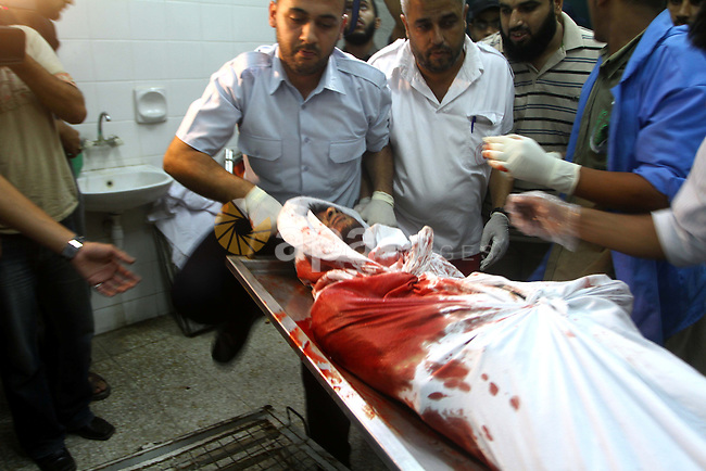 Palestinian men gather around the bodies of Emad Abu Abda and Anwar Isleem at the mortuary of Al-Aqsa hospital after they were killed when the Israeli air force targeted an area in the central Gaza Strip on August 19, 2011. Photo by Ashraf Amra