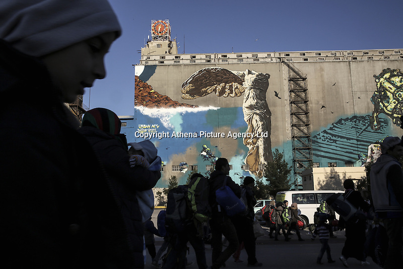Pictured: Silhouettes of migrants against a mural, as they arrive to the port of Piraeus Monday 22 February 2016<br /> Re: Thousands of migrants, most from Syria, have landed to the port of Pireaus, after crossing the border from Turkey to various islands like Lesvos and Kos in Greece.