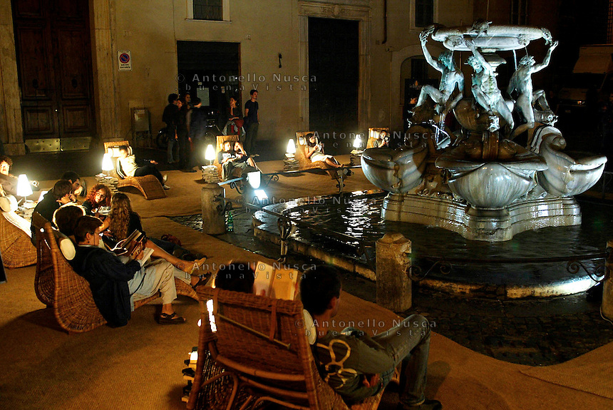 Rome continue to be one of the most visited city in the world..Roma continua ad essere una delle città più visitata al mondo,.Tourist reading books in front of the Tortoise Fountain during the first white night in Rome..Turisti leggono libri durante la prima notte bianca della capitale davanti la Fontana delle Tartarughe