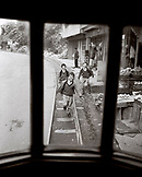 INDIA, West Bengal, school students chasing train on tracks, Darjeeling (B&W)