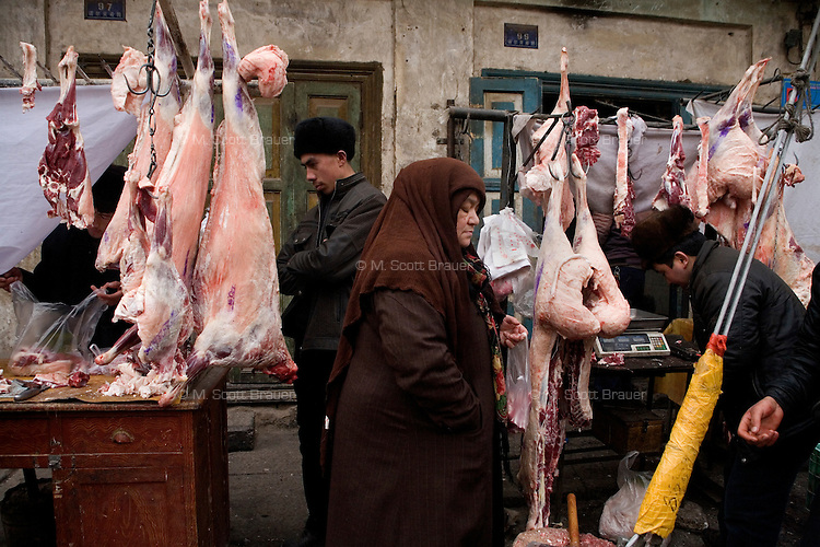 A butcher works on a sidewalk in the Old Town section of Kashgar, Xinjiang, China.