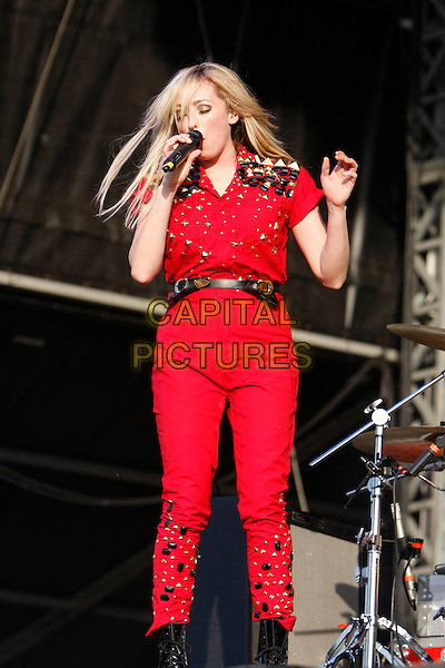THE TING TINGS - Katie White .Performing live at Wireless Festival in Hyde Park, London, England, UK, .July 2nd 2010..concert music gig live on stage half length 3/4  red shirt studded trousers waist belt gold studs singing microphone black high waisted hand .CAP/MAR.© Martin Harris/Capital Pictures.