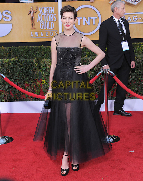 Anne Hathaway (wearing Giambattista Valli).Arrivals at the 19th Annual Screen Actors Guild Awards at the Shrine Auditorium in Los Angeles, California, USA..27th January 2013.SAG SAGs full length dress black sleeveless sheer tulle clutch bag bodice embroidered skirt hand on hip.CAP/DVS.©DVS/Capital Pictures.