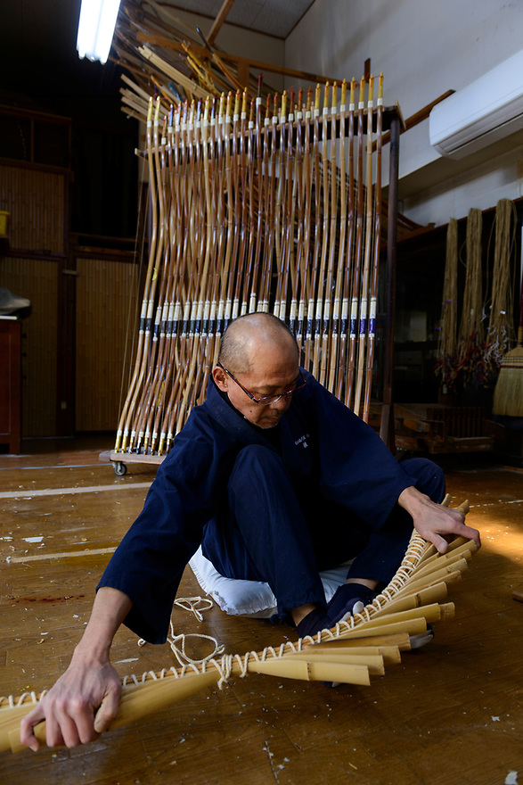 Reimei Yokoyama binding pieces of wood together for laminating as part of the bow making process. Wedges are knocked in with a mallet to keep the shape of the bow. Yokoyama Reimei Bowmakers, Miyakonojo, Miyazaki Prefecture, Japan, December 23, 2016. A handful of bowyers from the Kyushu city of Miyakonojo make over 90% of all the bows used in traditional Japanese archery. The bows are made from laminated bamboo and haze wood in process that consists of over 200 individual tasks. At over two meters from tip to tip the bows the longest used in the world.
