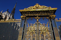 A typical gilt fence and a majestic golden gate with the main court of the Palais de Justice (Justice Palace) of Paris on the background. This is the Cour de Mai (Court of May), surmounted by the top of the back of the Sainte Chapelle. Digitally Improved Photo.