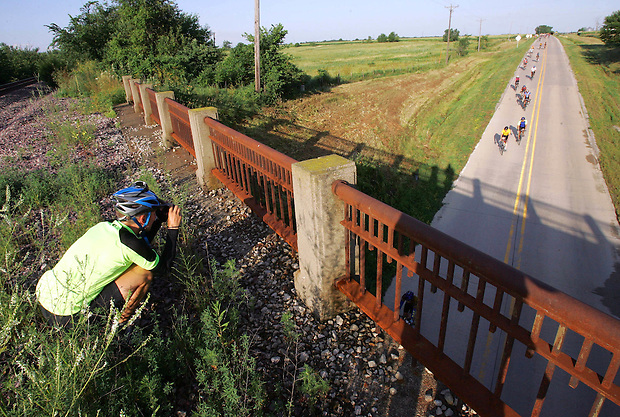 Dawn Westrum of Boone takes a photograph of riders from a railroad bridge west of Millerton Thursday morning on RAGBRAI XXXVII.