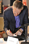 Erik Lindbergh (right), grandson of aviator Charles Lindbergh, writing autograph for Perry Los Kamp, the Past President of Mustang & Shelby Club of Long Island, at 85th anniversary celebration of Lindbergh's grandfather's historic solo flight across Atlantic, on Saturday May 19, 2012, at Cradle of Aviation museum, Long Island, New York.
