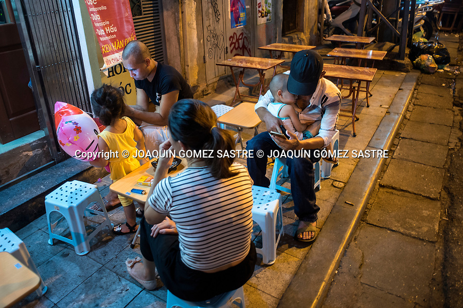 A Vietnamese family is watching their smartphone on a street in Hanoi,<br /> HANOI-VIETNAM