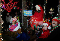 NWA Democrat-Gazette/DAVID GOTTSCHALK  Rachel Eaton, with the Fayetteville Public Library, reads a book Friday, November 20, 2015, on the library float as they participate in the Lighting Night parade of the Lights of the Ozarks on the downtown square in Fayetteville. The lights illuminate the square each evening from 5 p.m. to 1 a.m. through Dec. 31.
