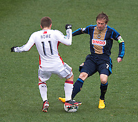 Brian Carroll (7) of the Philadelphia Union collides with Kelyn Rowe (11) of the New England Revolution during the game at PPL Park in Chester, PA.  The Philadelphia Union defeated the New England Revolution, 1-0.
