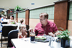 July 29, 2011. Cary, NC.. In one of the on campus cafeterias, Mark Fulp, feeds his 4 year old daughter Caitlyn lunch. She attends the on campus day care which is just seconds from the cafeteria.. Profile of SAS, a software company that has many amenities for its employees.