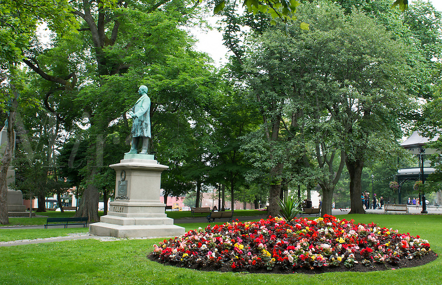 Canada Saint John New Brunswick Kings Square with flowers and Sir Samuel Leonard Tilley statue  and relaxing locals in quiet peaceful park.  Tilley one of founders of Confederate