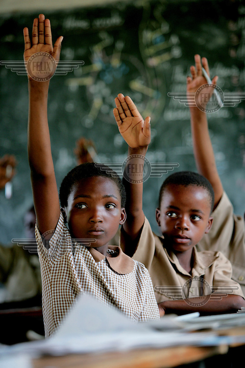 Kids raise their hands in a class in which most children have been affected by AIDS. Many are orphans..