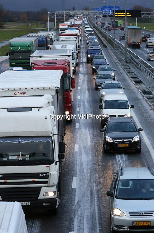 Foto: VidiPhoto<br /> <br /> VALBURG - Evenals donderdagochtend, kwam ook het verkeer donderdagmiddag tijdens de spits op veel plekken weer muurvast te staan, zoals hier op de A50 bij knooppunt Valburg. De hele dag door was er sprake van gladheid door winterse buien als sneeuw en hagel. Het KNMI gaf donderdagmorgen code geel uit voor gevaarlijk weer, maar dat bleek in de praktijk mee te vallen. Wel ontstonden er op de diverse snelwegen lange files. Ook de komende dagen wordt de nodige winterse neerslag verwacht.