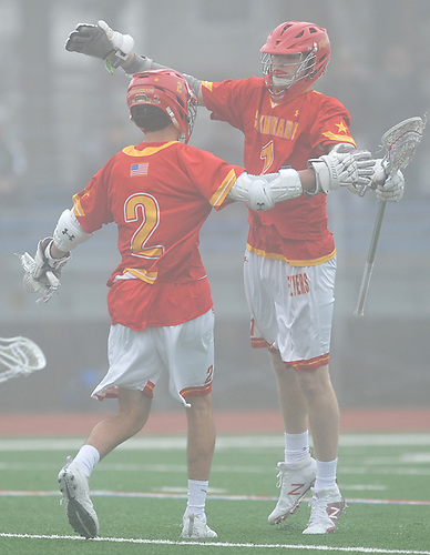 Aidan Byrnes #1 of Chaminade, right, congratulates teammate Jake Sexton #2 after he scored a goal in a non-league varsity boys lacrosse game against host Massapequa High School on Wednesday, April 4, 2018. Chaminade won by a score of 8-5.