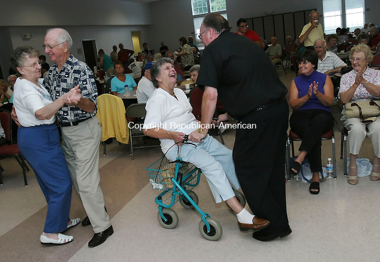 PLYMOUTH,  CT 28 August 2005 -082805BZ01-  Patricia Dolecki, of Terryville, laughs while being rolled around on her walker by Father Ron Zepecki, administrator of St. Pat's in Enfield, during the St. Casimir Church 11th annual fair Sunday afternoon. <br /> Jamison C. Bazinet / Republican-American