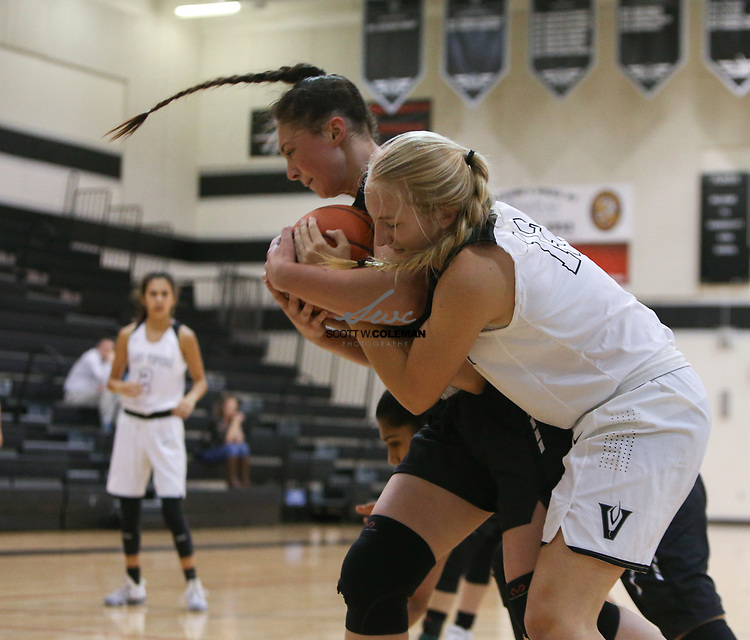 Vandegrift Vipers guard Jen Moore (12) and Cedar Park Timberwolves post Nicole Leff (40) tangle over a rebound during a girls high school basketball game between the Vandegrift Vipers and the Cedar Park Timberwolves at Vandegrift High School in Austin, Texas on November 14, 2017.