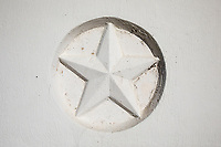 A weathered Texas Lonestar decorative emblem with paint faded and chipping off as found on a bridge in Austin, Texas. The Texas Lonestar is the official icon emblem of the great State of Texas.
