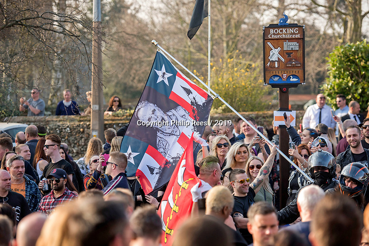 Prodigy fans with a flag with an image of Keith Flint during  the  funeral of the late Prodigy singer at St Marys Church in Bocking,  Essex today.