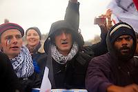 primo piano di manifestanti, uno con bandiera dipinta in volto e basco