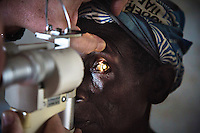 A woman has her eyes examined by ophthalmologist Doctor Richard Hardi in the remote village of Pania. <br /> <br /> From his base in Mbuji Mayi Hungarian ophthalmologist Friar Richard Hardi and his team travelled deep into the Congolese rainforest, by 4x4 and canoe, to treat people in isolated communities most of whom have never seen an ophthalmologist. At a small village called Pania they established a temporary field hospital and over the next three days made hundreds of consultations. Although both conditions are preventable, many of the patients they saw had Glaucoma or River Blindness (onchocerciasis) that had permanently damaged their eyesight. However, patients with cataracts, a clouding of the eye's lens, who were suitable for treatment were booked for an operation. For two days the team carried out the ten minute procedure on one patient after another. The surgery involves making a 2.2mm incision into the remove the damaged lens that is then replaced by an artificial one. Doctor Hardi is one of the few people willing to make such a journey but is inspired to do so by his faith and, as he says: 'Here I feel that I can really make a difference in people's lives'. /Felix Features