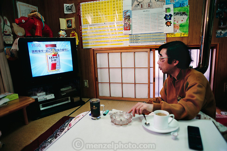 Kazuo Ukita's breakfast of coffee, cigarettes and television before work. There is a vitamin commercial on the TV. Japan. Published in Material World: A Global Family Portrait, Televisions of the World page 36. Food. The Ukita family lives in a 1421 square foot wooden frame house in a suburb northwest of Tokyo called Kodaira City.