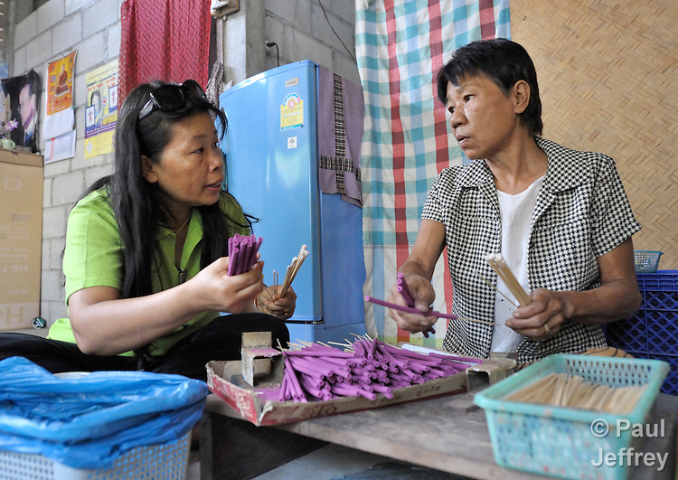 Nawanat Kunasawat (left), an outreach worker with the AIDS Ministry of the Church of Christ in Thailand, visits with Pranom Kantawong, a woman living with HIV in the city of Chiang Mai who is assembling incense sticks at home to earn income.
