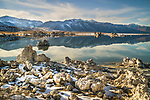 A close-up of small partially snowcovered tufas, with the Eastern Sierras reflected in Mono Lake. Partly blue sky with cirrus clouds.