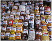 Brightly labelled, large clear bags of spices lined up for display in a Viet Nam marketplace.