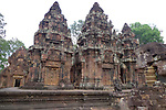 Angkorian temple Banteay Srei (late 10th century) 967.<br /> View from NW inner enclosure.Left is the northern library with pediment showing Krishna killing Kamsa. All three sanctuary towers have the same motif on the western side with pediments showing Varuna, gaurdian god of the west riding on geese.The lintels shows Ravana abducting Sita.<br /> Banteay Srei temple has three sanctuary towers.The central sanctuary and the southern sanctuary were dedicated to Shiva and the northern sanctuary was dedicated to Vishnu.<br /> Banteay Srei temple is situated 20km north of Angkor, built during the reign of Rajendravarman by Yajnavaraha, one of his counsellors. In antiquity Isvarapura was a small city that grew up around the temple. Banteay Srei was dedicated to the worship of Shiva, the foundation stele describes the consecration of the linga Tribhuvanamahesvara (Lord of the three worlds) in 967.