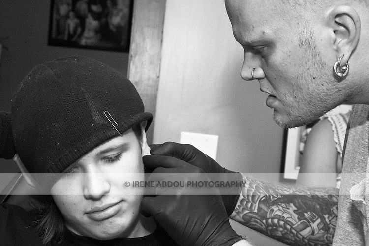 Body piercer Sean Jeweii pierces the ear of a teenager at a tattoo parlor in Rockland, Maine.