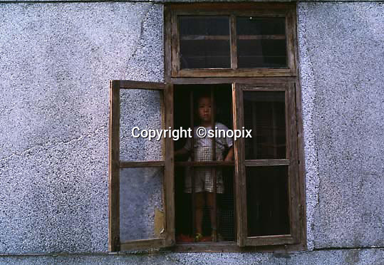 ONE OF THE DAUGHTERS OF A MAN WHO RETURNED FROM TRYING TO ESCAPE THE CLUTCHES OF THE BIRTH CONTROL COMMITTEE TO FIND THAT HIS HOUSE HAD BEEN DEMOLISHED.  THE NEWER CONCRETE AROUND THE WINDOW WAS REPLACED WHEN 30 MEMBERS OF THE BIRTH CONTROL COMMITTEE SMASHED HOLES INTO THE WALLS OF THEIR HOUSE.<br /> ©sinopix